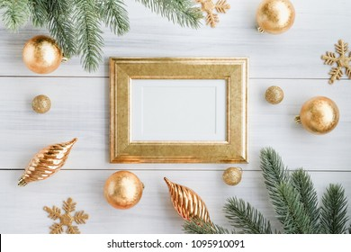 Top view of gold luxury blank frame, with gold decoration ball, gold ornament snowflake, pine brance on white wood table top,Flat lay ,holiday celebration still life,mock up for adding text,copy space