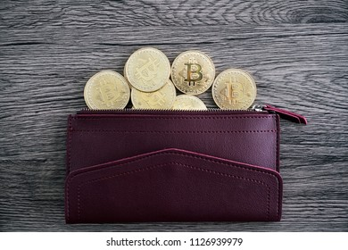 Top view of the golden bitcoins on the red leather wallet
