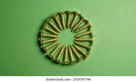 Top view of golden color slot drive Phillips flat head screw selective focus on some of the front screws on green background. All lay down on the surface perform a  beautiful circle shape