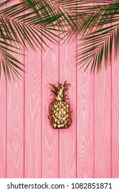 top view of golden pineapple and palm leaves on pink wooden surface