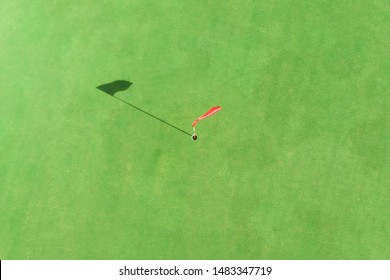 top view of golf pole on the green in a golf course with blank copyspace