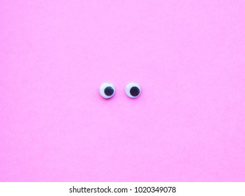 Top view of googly eyes on pink background with copy space.