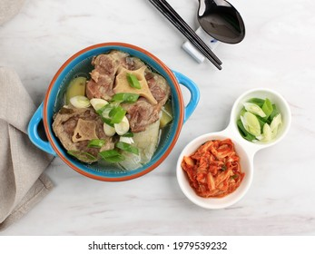 Top View Gori Gomtang (Sokkori Gomtang or Kkori) or Korean Beef Oxtail Stew  Soup, Served in the Blue Bowlwith Kimchi and Sliced Green Onion - Shutterstock ID 1979539232