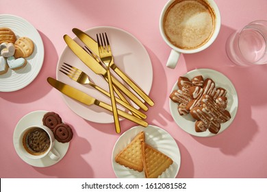 Top view of gourmet cookies and biscuits with coffee and water on pink surface