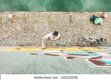 Top view of graffiti artist painting with color spray on the wall - Urban, street art, millennials generation, mural concept - Focus on his head