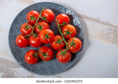 a top view of grape of cherry tomatoes on the blue plate