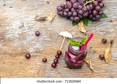 top view of grape juice in glass jar on old wood. dried leaf autumn concept. copy space for text