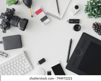 top view of graphic design concept with digital camera, memory card, smartphone, graphic tablet, external harddisk, pantone book and keyboard on white background with copy space