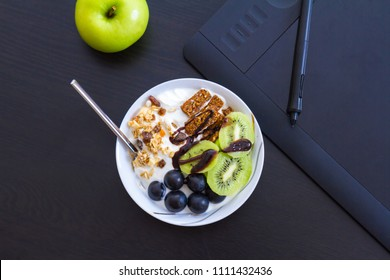 Top view of graphic design and healthy lifestyle concept, close up view of cup with raw bars and grape, kiwi fruits inside. Tablet and green apple behind.