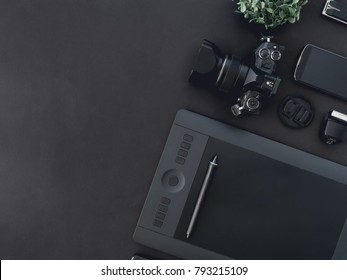 top view of graphic design work station, work space concept with digital camera, memory card, graphic tablet on black background with copy space