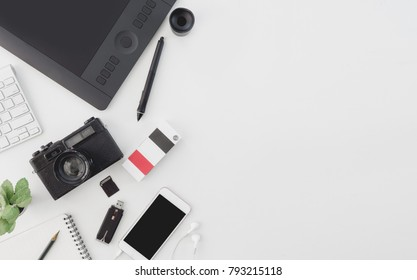 top view of graphic design work station, work space concept with retro camera, book, memory card, smartphone, graphic tablet, external harddisk on white background