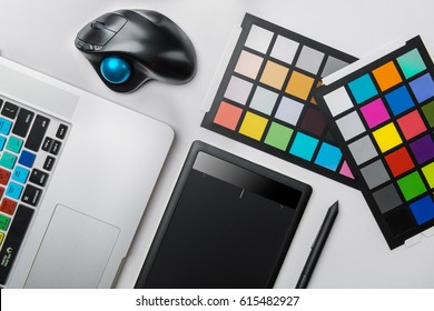 Top view of graphic designer desk. Laptop, trackball mouse, digital graphic tablet
