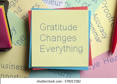 Top view of Gratitude Changes Everything written on a note with a pen aside.