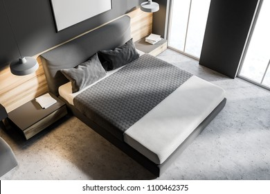 Top view of a gray bedroom corner with a concrete floor, a king size bed and a frame vertical poster hanging above it. 3d rendering mock up
