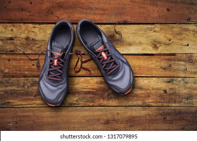 Top view of gray and orange trainers on a wooden background.
