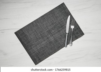 Top view of gray placemat table mat with knife and fork on white wooden table
