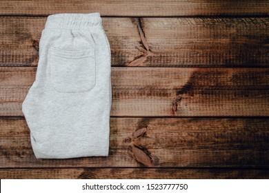 Draufsicht auf grauem Pullover auf Holzhintergrund. Kinderpullis mit sichtbaren zwei Beinen.