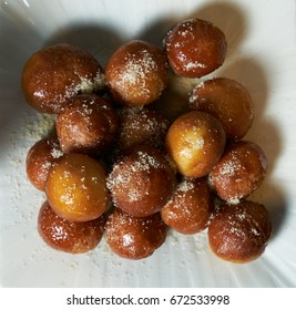 Top view of a Greek loukoumades donuts with honey and cinnamon close-up on a white plate. horizontal view from above