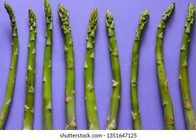 Top view of green asparagus against purple background