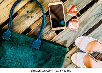 Top view green big casual bag with snake print, round glasses, golden phone and pair of female high-heeled shoes on a wooden background. Modern fashion concept and everyday women's clothing and acce