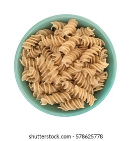 Top view of a green bowl filled with uncooked brown rice pasta fusilli isolated on a white background.