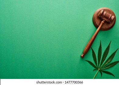 top view of green cannabis leaf near wooden gavel on green background with copy space