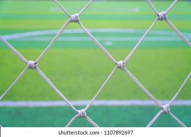 Top view of green soccer field.Beautiful artificial grass on the stadium.Abstract football turf ground background with white stripe line and net.Background,Sport,Texture Concept