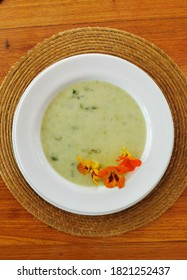 Top view of green soup with comestible flowers