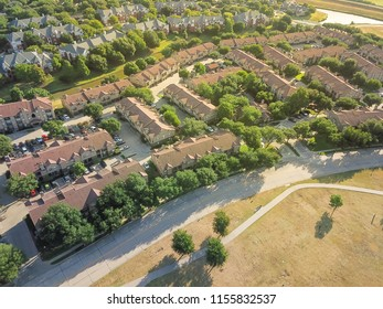 Top view green suburb growing with community park, apartment complex and canal. Aerial subdivision in Irving, Texas, USA