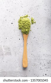 Top view of green tea matcha in a spoon on concrete surface. It is a rich source of antioxidants and polyphenols. When preparing, the powder is partially dissolved in hot water
