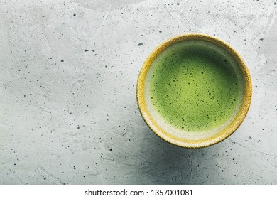 Top view of green tea matcha in a bowl on concrete surface. It is a rich source of antioxidants and polyphenols