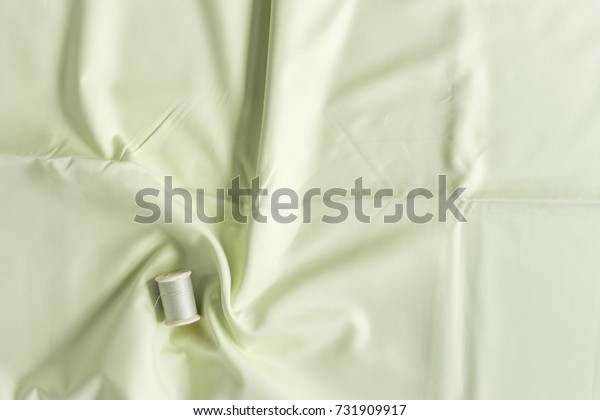 top view of green thread matching with green cotton fabric for sewing. copy space for text and background