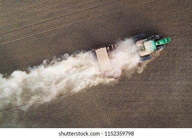 Top view of green tractor working in fields. Aerial photo.