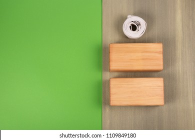Top view of green yoga mat, two wooden blocks and white belt on green background with copy space. Yoga practice, relaxation and meditation concept