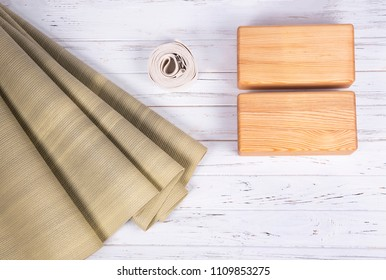 Top view of green yoga mat, two wooden blocks and white belt on white wooden  background with copy space. Yoga practice, relaxation and meditation concept
