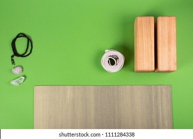 Top view of green yoga mat, crystals, mala,  two wooden blocks and white belt on green background with copy space. Yoga practice, pilates, relaxation and meditation concept.