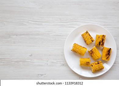 Top view, grilled corn on the cob on round white plate over white wooden background. Summer food. From above, overhead. Copy space.