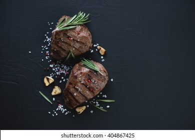 Top view of grilled filet mignon beefsteaks on a black wooden surface