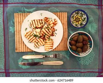 Top view of grilled halloumi cheese, olives and olive oil on a turquoise cloth with pearl handled cutlery