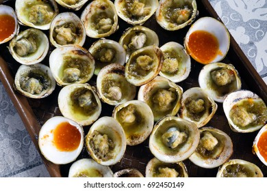 Top view of grilled Hard-Shell Clams / Quahogs / Round Clams (Mercenaria mercenaria) with chili sauce.