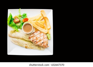 Top view of grilled pork and salmon fillet with greens and fresh vegetables on isolated black background.  copy space .