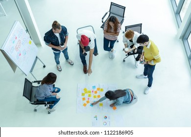 Top view Group Of Asian and diverse Business people with casual suit brainstorming and helping to put postit paper on the project chart together in the modern workplace, multiethnic teamwork concept