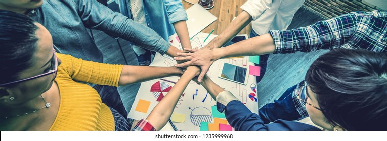 Top view of Group Of Asian and Multiethnic Business people making pile of hands in the modern office, people business teamwork group concept, Banner and web page or cover template