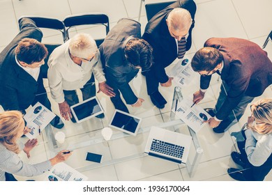 top view. group of employees discussing financial statistics .