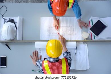 Top view of group of engineering team is meeting, planning construction work, Architects looking paper plans at construction site, overhead view,Concept for team work