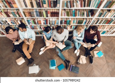 Top view group of ethnic multicultural students sitting near bookshelf in library.