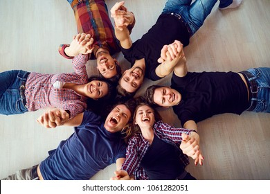 Top view. A group of friends are laughing lying on the floor.