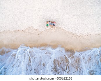Top view of group of happy friends lying on the beach near the stormy sea and dreaming. Aerial view two couples relax on the beach.
