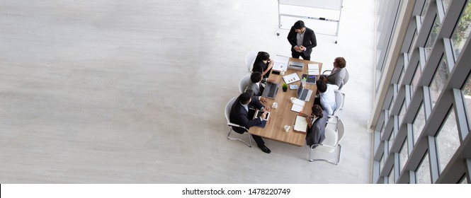 Top view of group of multiethnic busy people working in an office, Aerial view with businessman and businesswoman sitting around a conference table with blank copy space, Business meeting concept