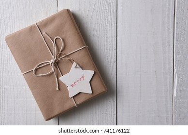 Top view of a group of a paper wrapped Christmas presents with a wood gift tag stamped with the word Merry.